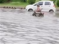 河南太康马路被雨淹,大妈骑轮椅涉水而行,一脸无畏引路人围观